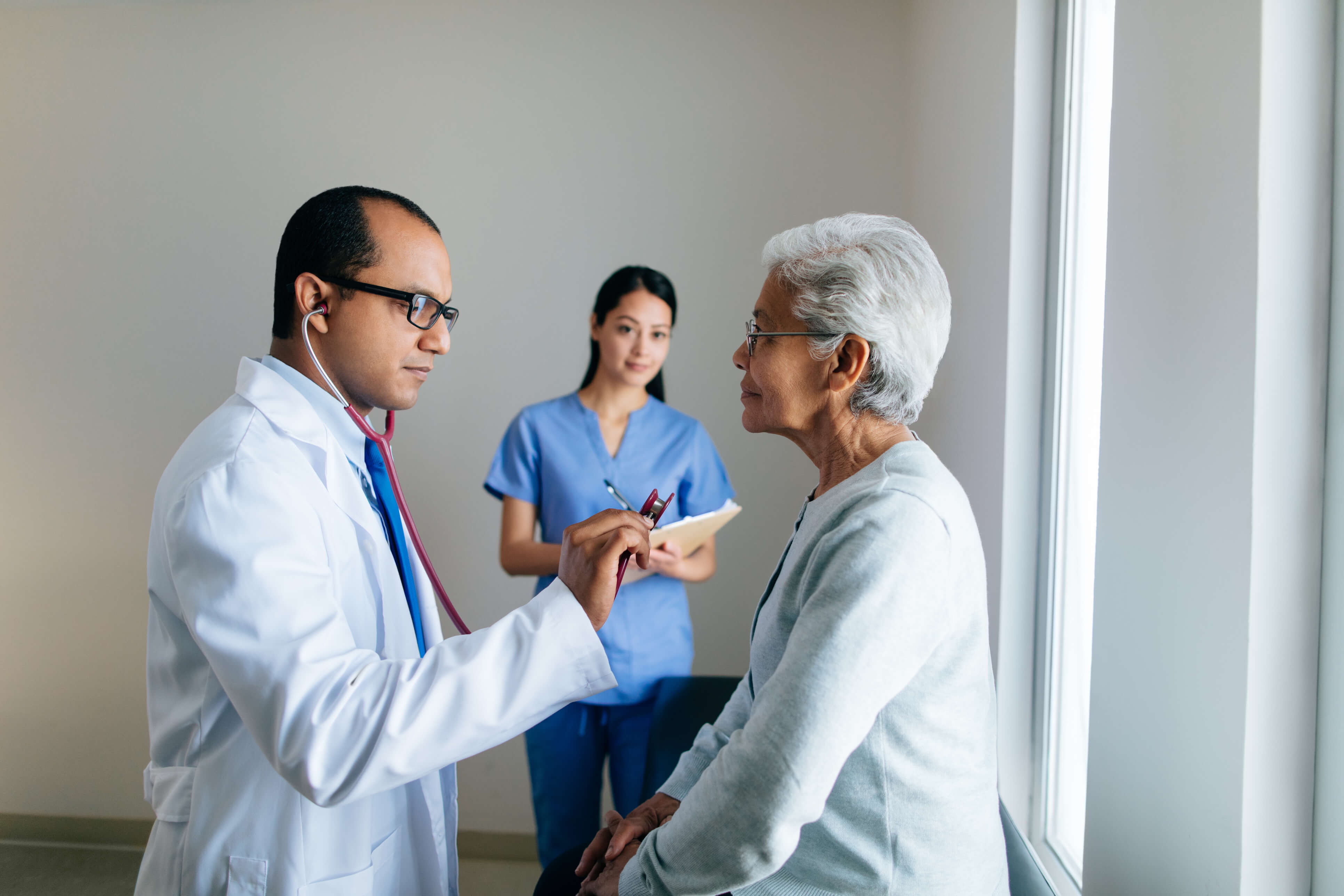 Male doctor consulting patient with Physician Assistant
