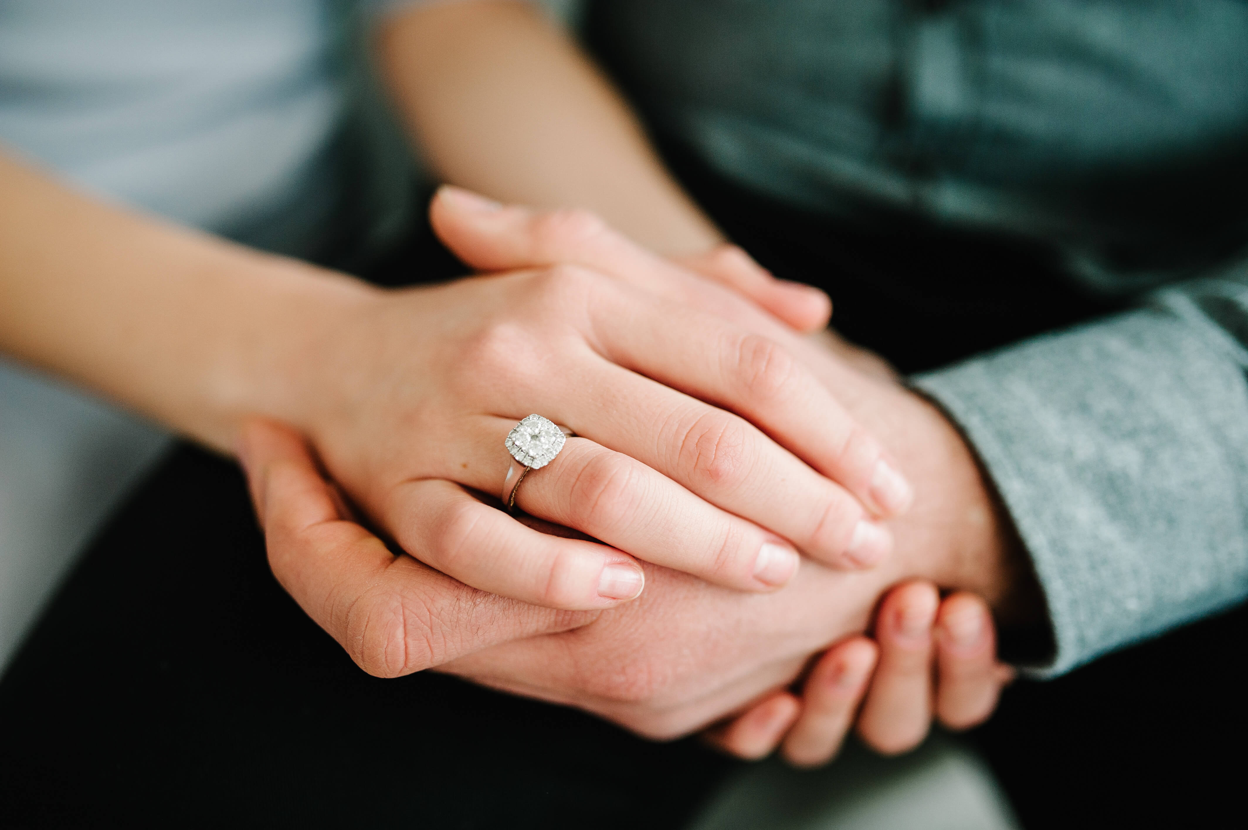 Couple holding hands wearing wedding ring